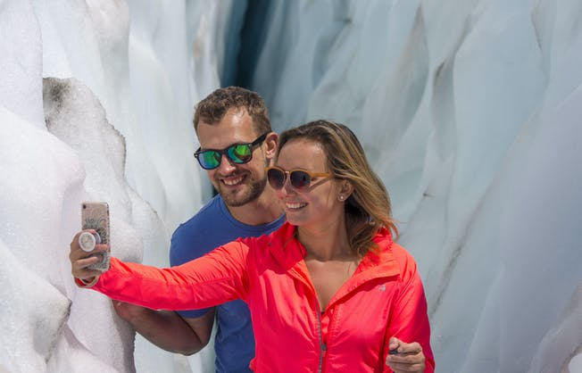 A couple in their mid-thirties take a selfie snap while touring Franz Josef Glacier