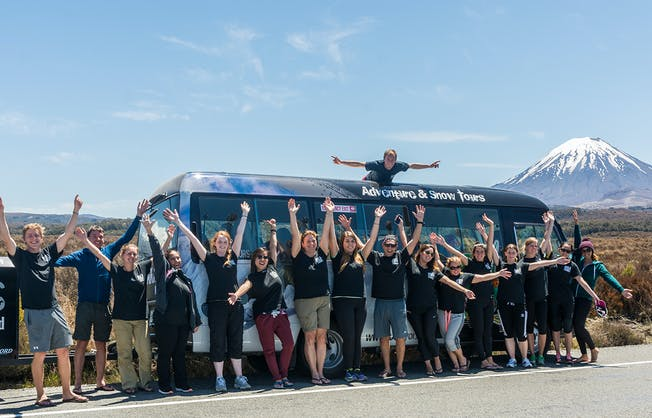 A group of people with their arms raised in joy stand in front of a New Zealand tour bus with a Mount Ngauruhoe in the distance
